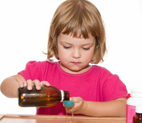 Девочка наливает лекарство в ложку